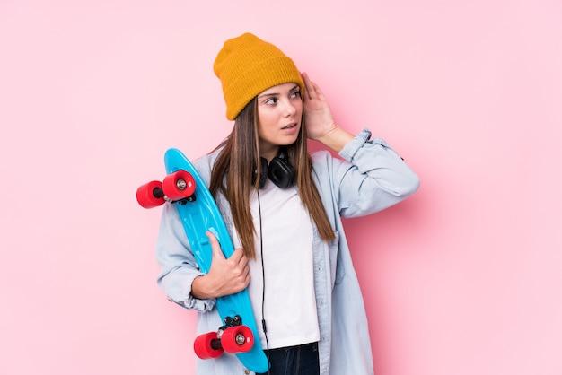 Молодая фигуристка женщина держит скейт, пытаясь слушать сплетни.