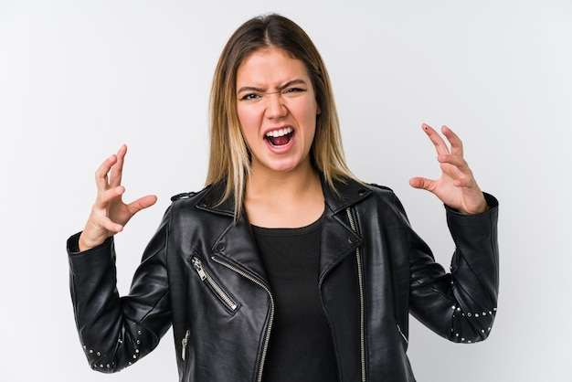 Молодая кавказская женщина нося черную кожаную куртку кричащую с яростью.