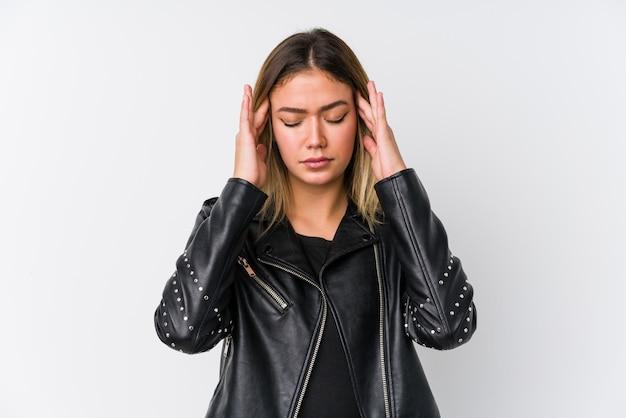 Молодая кавказская женщина нося виски черной кожаной куртки касающие и имея головную боль.