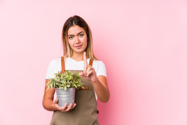 Молодая кавказская женщина садовника в розовом показе стены одно с пальцем.