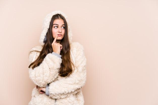 若い白人女性が疑わしいと懐疑的な表情で横に孤立したポーズをポーズします。