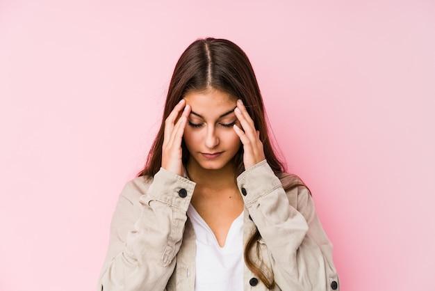 Молодая кавказская женщина представляя в висках розовой стены касающих и имея головную боль.