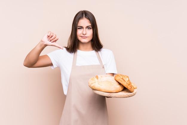 Молодая кавказская женщина хлебопека изолировала показывать жест нелюбов, большие пальцы руки вниз. концепция несогласия.