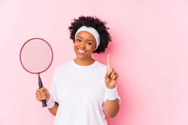 Молодая афро-американская женщина играя бадминтон изолировала показывать одно с пальцем.