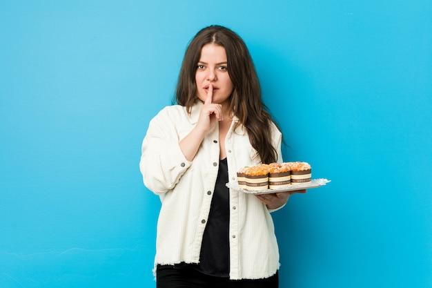 秘密を保持または沈黙を求めてカップケーキを保持している若い曲線の女性。