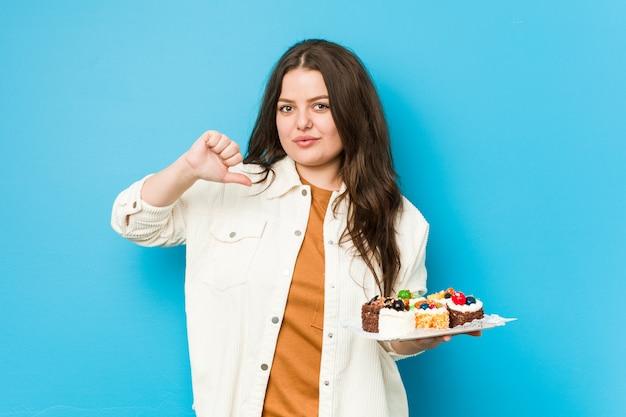 甘いケーキを保持している若い曲線の女性は、誇りに思って、自信を持って、次の例です。