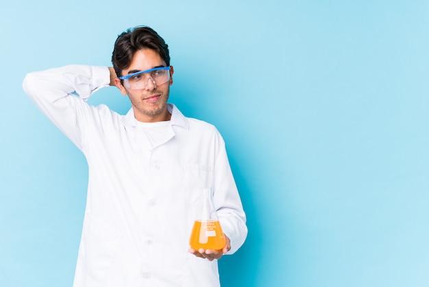 科学者の若い白人男は、頭の後ろに触れて、考えて、選択を分離しました。