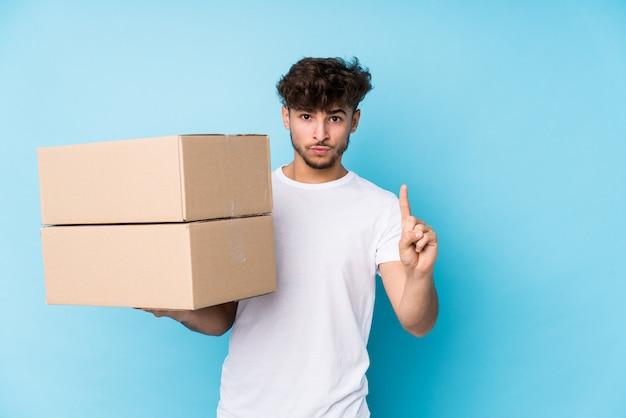 Молодой арабский человек держа коробки изолировал показывать одно с пальцем.