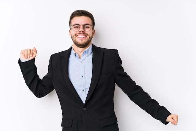 Молодой человек кавказской бизнес, ставит в белой стене изолированные молодой человек кавказской бизнес, танцы и весело.