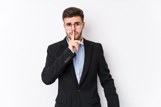 孤立した白い壁でポーズをとる若い白人ビジネスマン秘密を守るか沈黙を求める若い白人ビジネスマン。
