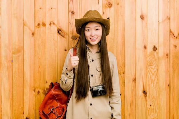 Молодая китайская женщина путешественника усмехаясь и поднимая большой палец руки вверх