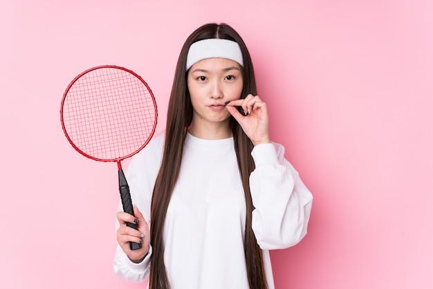 Молодая китайская женщина играя бадминтон изолированный с пальцами на губах держа секрет.