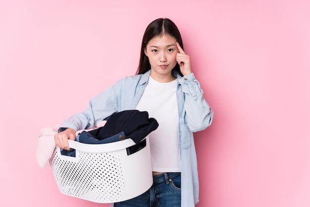 Молодая китайская женщина выбирая вверх пакостные одежды изолировала указывать висок с пальцем, думая, сфокусированный на задаче.