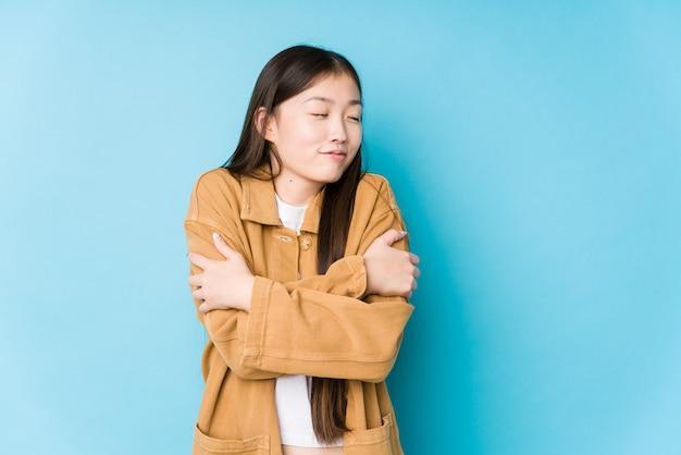 Молодая китайская женщина позирует в синей стене изолированные объятия, улыбаясь беззаботной и счастливой.