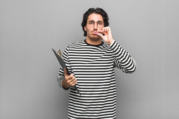 Молодой сотрудник мужчина держит инвентарь с пальцами на губах, сохраняя в тайне.