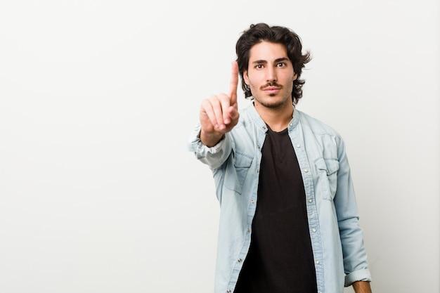 Молодой красивый человек против белой стены показывая номер один с пальцем.