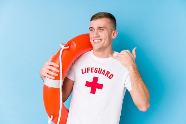 Молодой спасатель мужчина держит спасательный поплавок, показывая жест мобильного телефона с пальцами.
