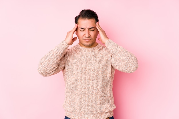 Молодой соблазнительный мужчина позирует в розовой стене изолированные трогательные храмы и головная боль.
