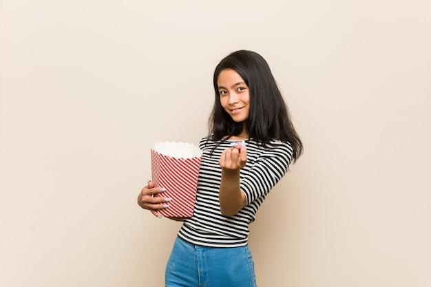 Молодая азиатская девушка держа ведро попкорна указывая с пальцем на вас как будто приглашая приблизиться.