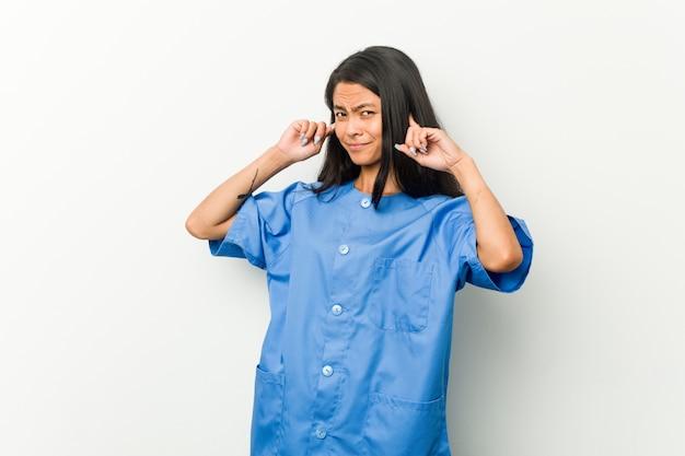 若いアジアの看護師の女性の手で耳を覆っています。
