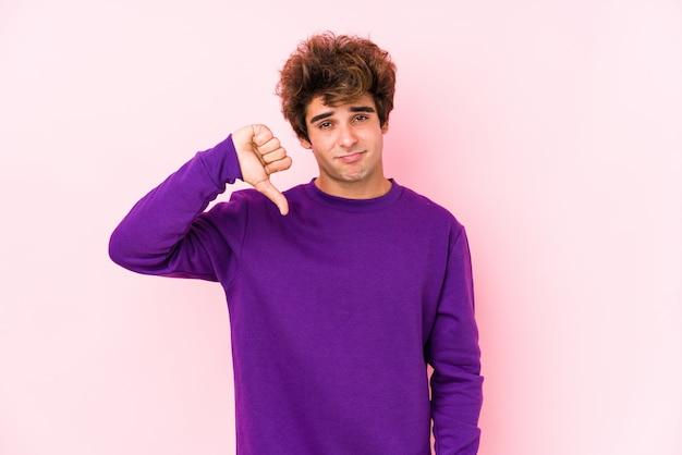 嫌いなジェスチャー、親指ダウンを示す分離されたピンクの壁に若い白人男。不一致の概念。