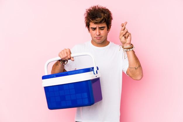 幸運のために指を渡るポータブル冷蔵庫を保持している若い白人男