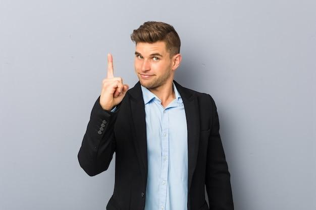 Молодой красивый кавказский человек показывая номер один с пальцем.