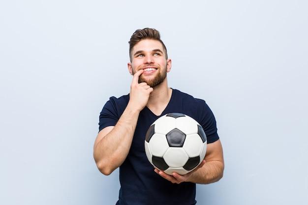 Молодой кавказский человек держа футбольный мяч ослабил думать о что-то смотря космос экземпляра.