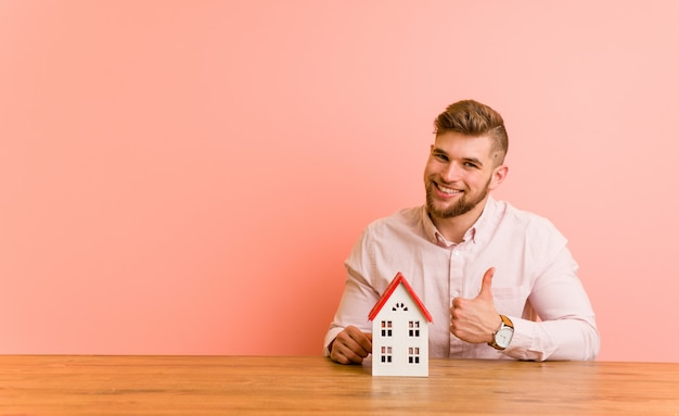 笑みを浮かべて、親指を上げる家アイコンと座っている若い白人男