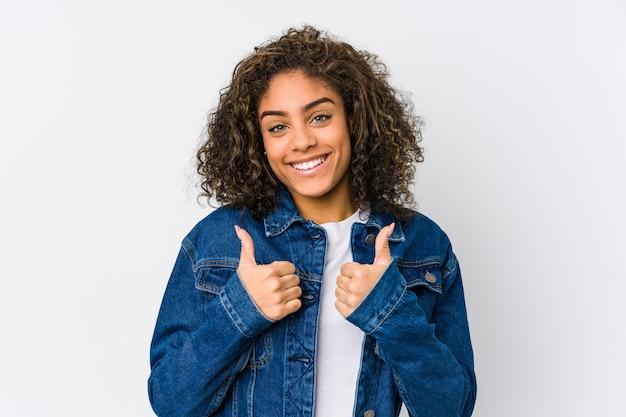 Молодая афро-американская женщина поднимая оба больших пальца руки вверх, усмехаться и уверенно.