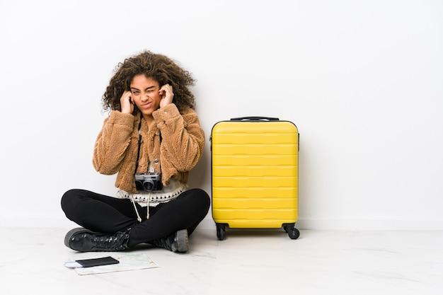 若いアフリカ系アメリカ人女性の手で耳をカバーする旅行の準備ができて。