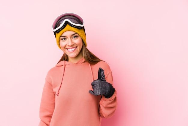 Молодая кавказская женщина нося одежду лыжи изолировала усмехаться и поднимать большой палец руки вверх