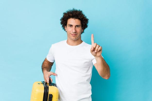 Молодой человек средних лет, держащий показ чемодана номер один пальцем.