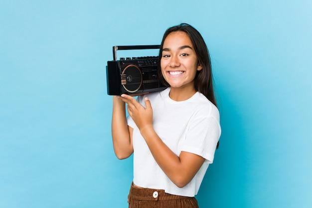 分離されたヴィンテージのカセットを保持している若いインド人女性