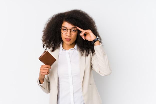 クレジット車を保持している若いアフロビジネス女性が分離指で思考を指して、クレジットカーポインティング寺院を保持している若いアフロビジネス女性がタスクに焦点を当てています。