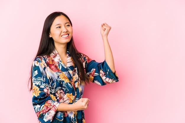 Молодая китайская женщина нося пижаму кимоно изолировала поднимать кулак после победы, концепцию победителя.