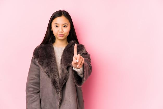 Молодая китайская женщина нося пальто изолировала показывать одно с пальцем.