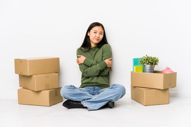Молодая китаянка переезжает в новый дом обнимает, улыбаясь беззаботно и счастливо.