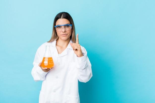 指でナンバーワンを示す若い科学的な女性。