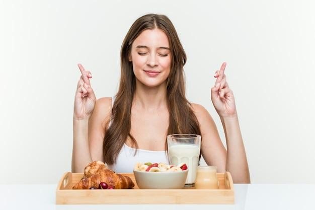 Молодая кавказская женщина имея пальцы скрещивания завтрака для иметь удачу