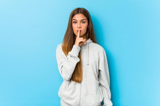 若いスポーティな女性が秘密を守るか沈黙を求めています。