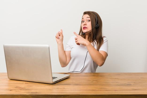 Молодая женщина телемаркетер шокирован, указывая указательными пальцами на копией пространства.