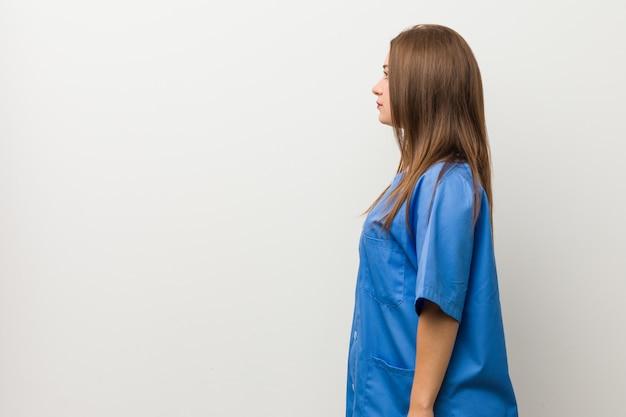左を見つめる白い壁に若い看護師の女性、横向きのポーズ。