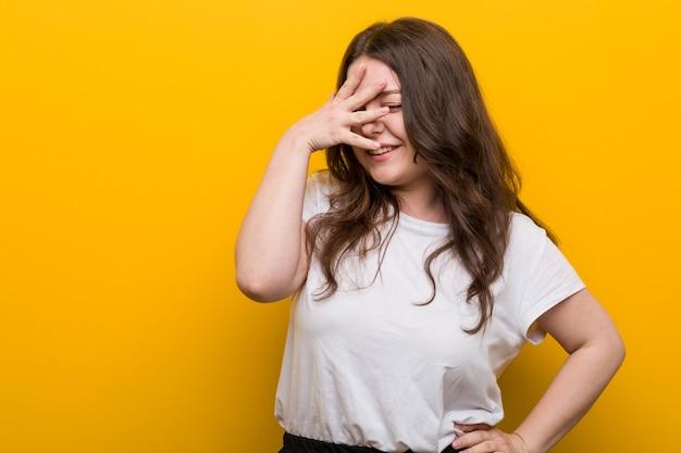 若い曲線美のプラスサイズの女性は、恥ずかしい顔を覆っている指を通してカメラで点滅します。