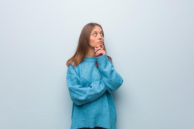 疑って混乱している青いセーターを着ている若いきれいな女性