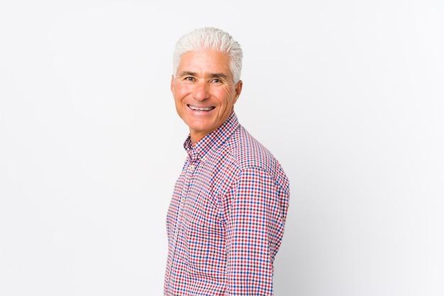 分離されたシニア白人男は笑みを浮かべて、陽気で快適な脇に見えます。