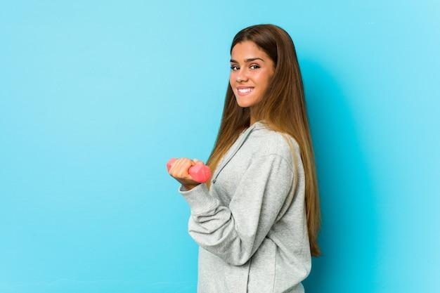 青い壁に分離されたダンベルを保持している若い白人女性