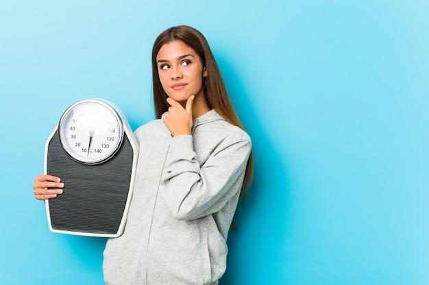 Молодая женщина фитнеса держа масштаб смотря косой с сомнительным и скептическим выражением.