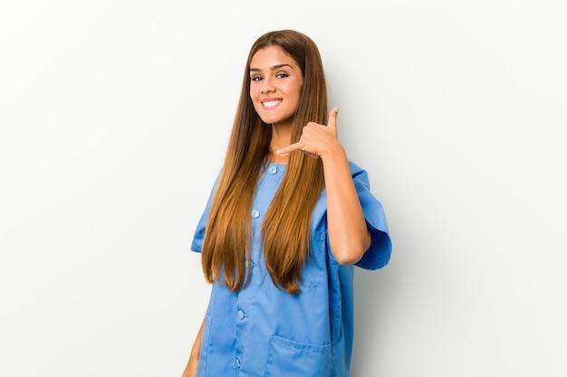 指で携帯電話のジェスチャーを示す若い白人看護師の女性。