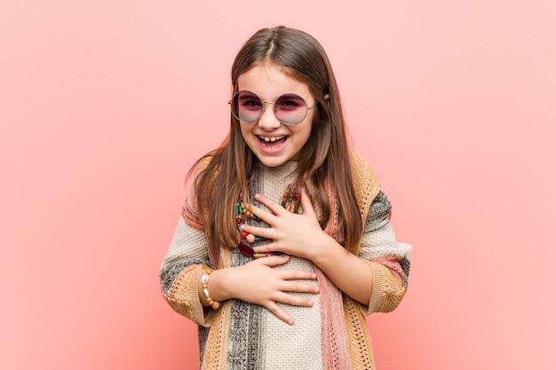 Маленькая хиппи девушка радостно смеется и весело держит руки на животе.